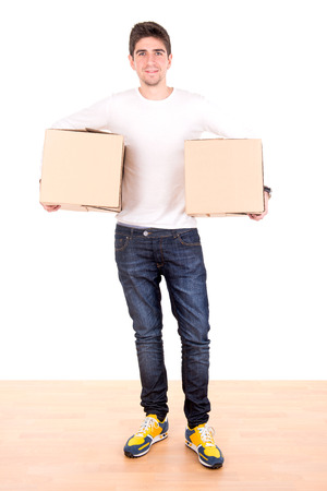unpacking: Handsome young man with cardboard boxes unpacking in new home Stock Photo