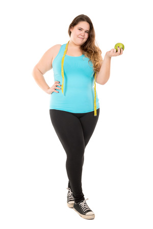gluttonous: Beautiful large girl with measuring tape and apple isolated in white Stock Photo