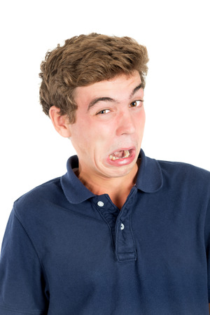 disgusted: Disgusted teenage boy making faces isolated in white