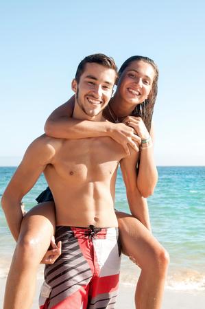 pareja adolescente: Pares adolescentes felices jugando en la playa