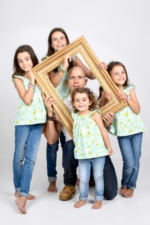 siblings: Siblings and dad posing with a frame Stock Photo