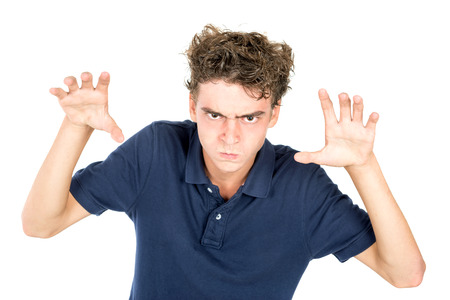 angry kid: Angry teenage boy making faces isolated in white