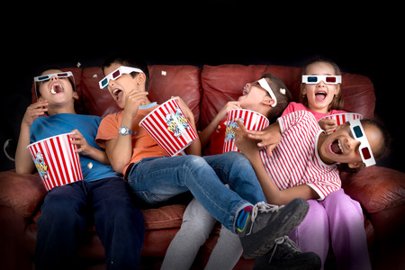 Group of children with 3d glasses and popcorn in a sofa having fun