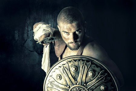 gladiator: Gladiator posing with shield and sword in a dark background