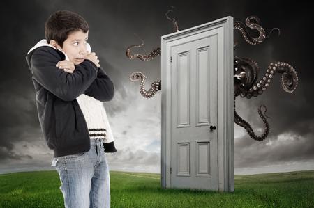 asustado: El muchacho joven que teme un monstruo detr�s de una puerta
