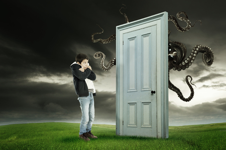 fearing: Young boy fearing a monster behind a door