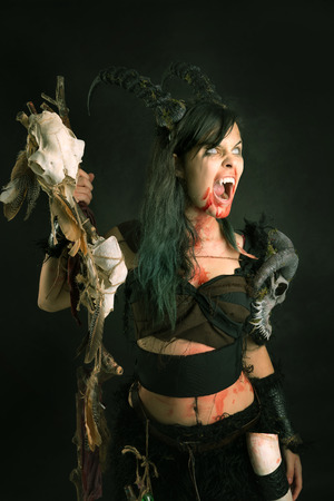 faun: Faun sorceress with big horns and blood against a dark background