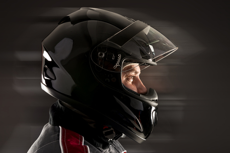 Racing driver posing with helmet isolated in black