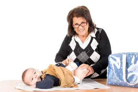 changing diaper: Grandmother changing baby diaper isolated in white