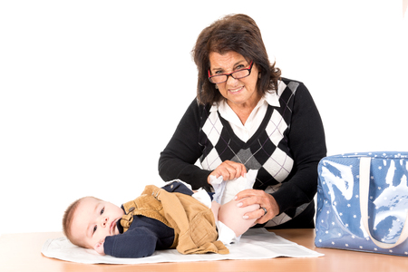 diaper changing: Grandmother changing baby diaper isolated in white