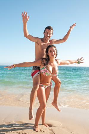 pareja de adolescentes: Pares adolescentes felices jugando en la playa