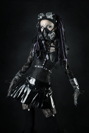 Cyber Gothic girl posing isolated in a dark background