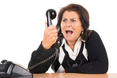 Angry senior woman with old telephone isolated in white