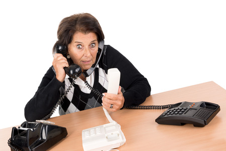 desesperado: Desperate senior woman with several phones isolated in white