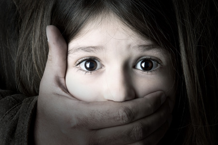 Scared young girl with an adult man's hand covering her mouth