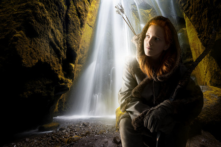 Fantasy girl archer in a waterfall with bow Stock Photo