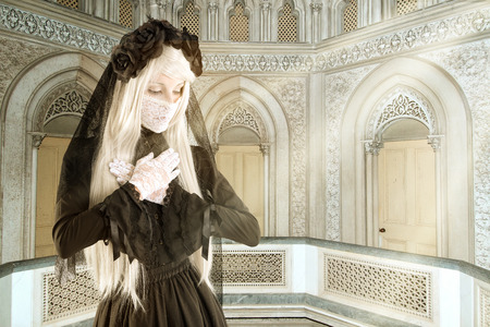 Girl in a widow black dress with white eyes looking like a doll Stock Photo