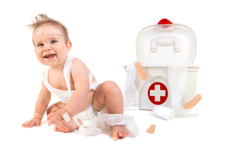 Cute baby boy playing with bandages in a first aid kit box. Stock Photo