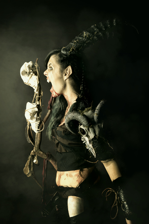 Faun sorceress with big horns and blood against a dark background