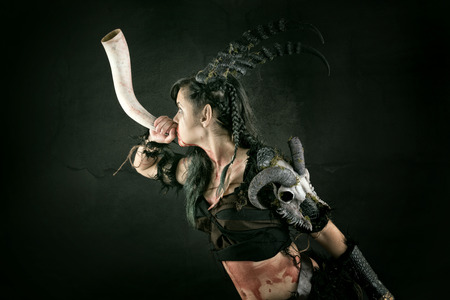 Faun sorceress with big horns blowing a horn Stock Photo