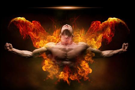 Mocny atletyczny mężczyzna z wielką sylwetką. Silny kulturysta z otwartymi ramionami i otoczony ogniem