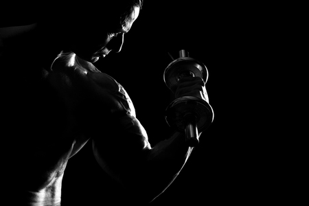 Muscle man doing bicep curls with backlight. Stock Photo