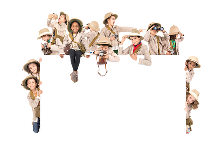 Childrens group with safari clothes and gear over a white board Imagens