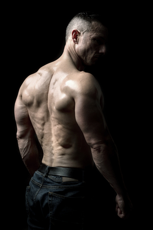 Power athletic man with great physique. Strong bodybuilder showing his shoulders and back