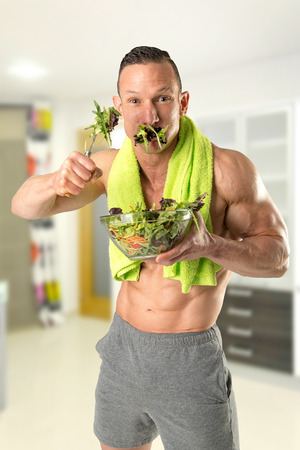Powerful athletic man with great phisique eating a healthy salad.