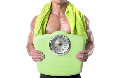 Powerful athletic man with great phisique holding a weight scale and towel.