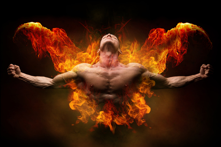 Power athletic man with great physique. Strong bodybuilder with open arms and surrounded by fire