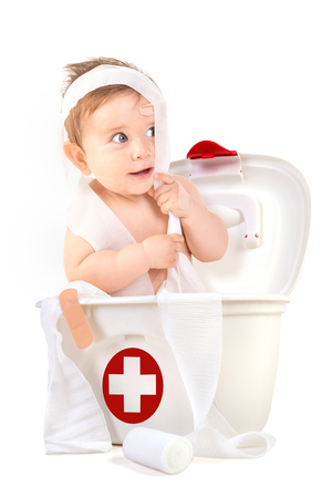Cute baby boy playing with bandages in a first aid kit box. Фото со стока