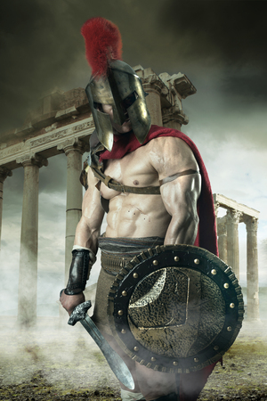 Ancient warrior or Gladiator posing outdoors with helmet Imagens