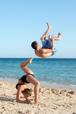 Couple having fun doing jumps in the beach Banco de Imagens - 80026216