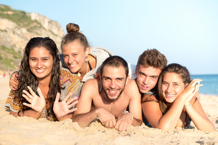 Group of happy teenage friends having fun at the beach