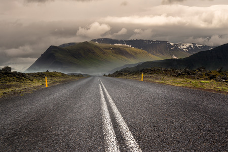 Empty road with cloudy skies and mountains Stock Photo