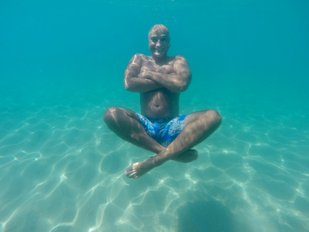 Underwater image of a happy man diving  photo