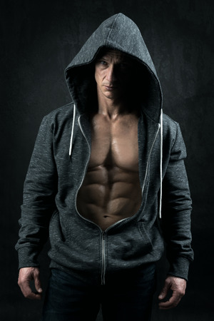 Power athletic man with hoodie showing six pack, perfect abs over a grunge background