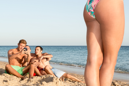 Group of boys checking a girl in the beach Stock Photo