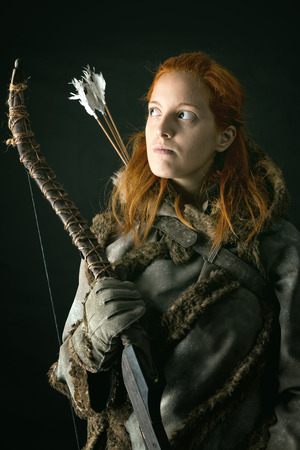 girl archer in a costume with bow isolated in a dark background Stock Photo