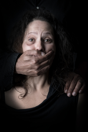 Scared woman with mans hand covering her mouth, victim of domestic violence