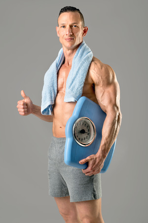 Powerful athletic man with great physique holding a weight scale isolated.
