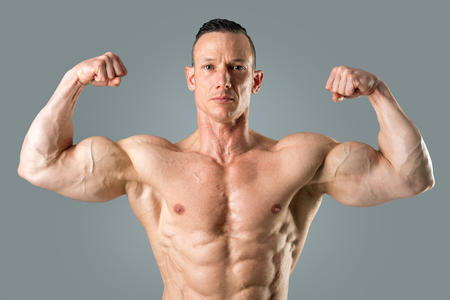 Powerful athletic man with great physique. Strong bodybuilder showing his biceps.