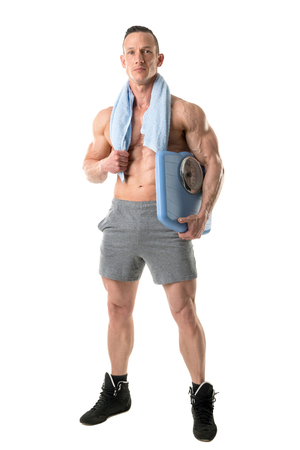 Powerful athletic man with great physique holding a weight scale isolated in a white background Banco de Imagens