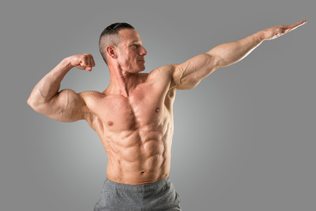 Powerful athletic man with great physique. Strong bodybuilder with six pack, perfect abs, shoulders, biceps, triceps and chest. Stock Photo