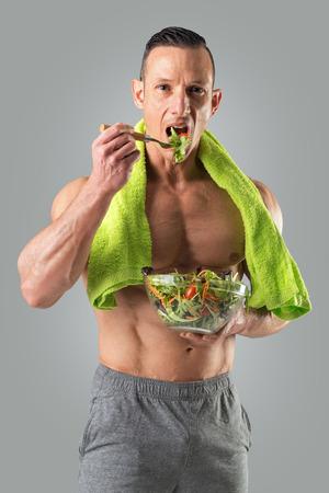 건강 한 샐러드를 먹는 훌륭한 체격을 가진 강력한 운동 남자. 스톡 콘텐츠