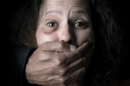 Scared vrouw met man's hand die haar mond bedekt, slachtoffer van huiselijk geweld