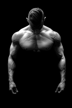 Power athletic man with great physique. Strong bodybuilder showing perfect body isolated in black.