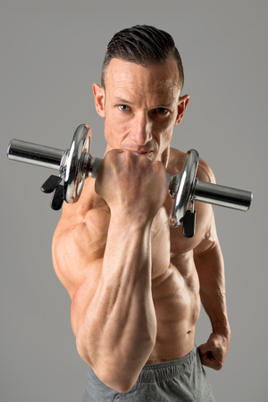 man with powerful biceps using dumbbell