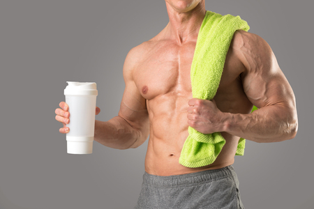 Powerful athletic man with great physique holding a gym bottle Stock Photo